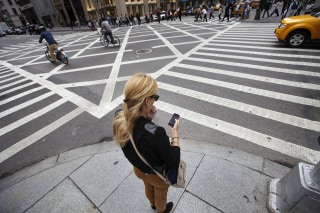 Image: A woman uses her Apple iPhone while waiting to cross 5th Avenue in New York