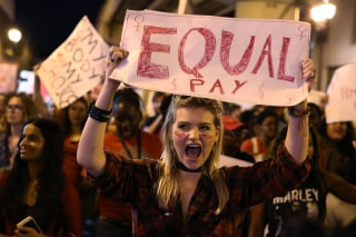 "Image: A protester holds a sign that readings ""Equal Pay"""