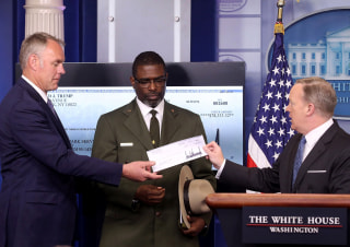 Image: White House press secretary Sean Spicer gives Interior Secretary Ryan Zinke the first quarter check of President Trump's salary, which he donated to the National Park Service, as Tyrone Brandyburg looks on.