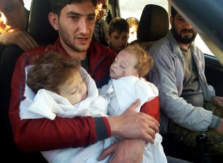 Image: Abdul-Hamid Alyousef holds his twin babies who were killed during a suspected chemical weapons attack in Syria