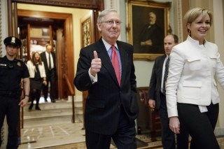 Image: Mitch McConnell signals a thumbs-up as he leaves the Senate chamber on Capitol Hill