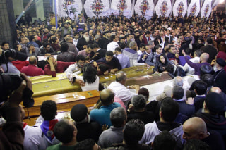 Image: Egyptian Christians mourn by caskets during the funeral of some of the victims.