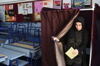 Image: A woman holds her ballot in the referendum on expanding the powers of Turkey's president.