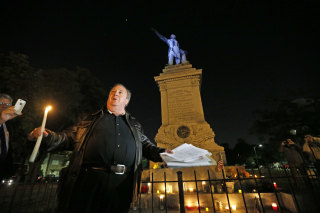 Image: Charles Lincoln speaks during a candlelight vigil