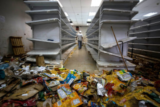 Image: A man walks down the aisle of a destroyed grocery store