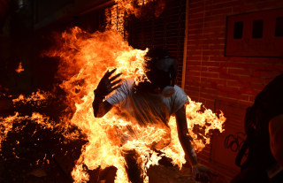 Image: A demonstrator catches fire during clashes with police