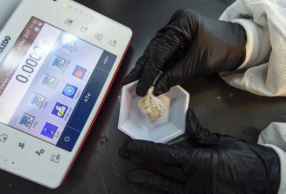 """Image: A forensic chemist prepares a sample of the drug """"gray death"""" to be weighed at the crime lab of the Georgia Bureau of Investigations"""