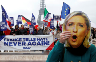 "Image: A protester holds a Marine Le Pen mask near banner reading ""France Tells Hate: Never Again"""