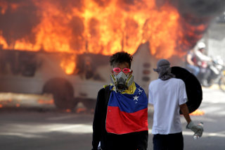 Image: Fiery protests in Caracas were among many across Venezuela on Monday.