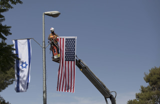 Image: A municipal worker hangs the U.S. and the Israeli flags in Jerusalem