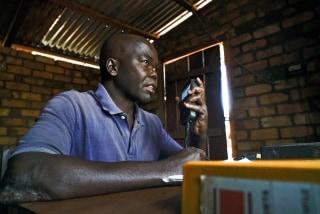 Image: Firmin Gbiara operates the radio in Obo