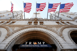 Image: Flags fly above the entrance to the new Trump International Hotel on its opening day in Washington