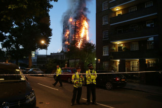 Image: Police maintain a security cordon as a huge fire engulfs the Grenfell Tower