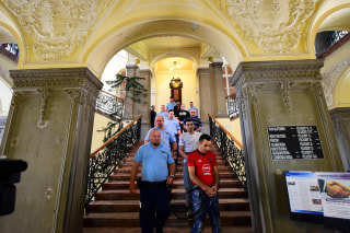 Image: Suspected smugglers are led into a Hungarian courthouse by police at the start of their trial.