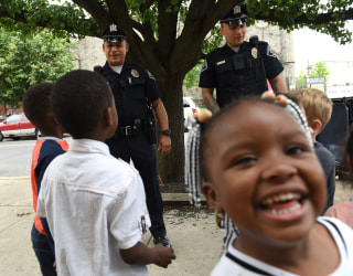 Image: A schoolgirl smiles as Camden County Police Department officers are seen on foot patrol in Camden