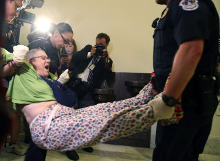 Image: U.S. Capitol Police remove a woman from a protest in front of the office of Senate Majority Leader Mitch McConnell