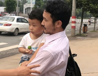 Image: Activist Hua Haifeng carries his son Bobo as they leave a police station in Ganzhou, China.