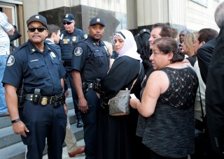 Image: Family members of detainees line up to enter the federal court just before a hearing to consider a class-action lawsuit filed on behalf of Iraqi nationals facing deportation, in Detroit