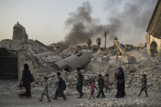 Image: Fleeing civilians walk past Mosul's heavily-damaged al-Nuri mosque during Iraq's war on ISIS