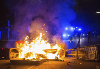 Image: Policemen stand behind a burning barricade in Hamburg.