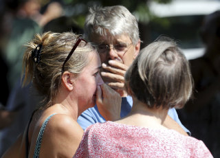 Image: Former Minnehaha Academy employees Elizabeth Van Pilsum, left, and Rick Olson, center, react after an explosion at the schoo