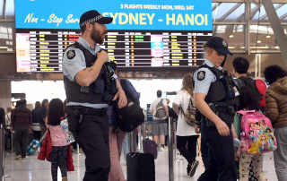 Image: Police walk past passengers as they patrol Sydney Airport
