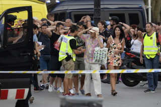 Image: Policemen check the identity of people standing with their hands up after a van struck pedestrians, killing at least 13 people