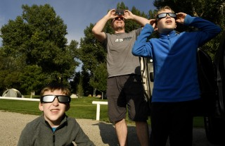 Image:Eric Romberg teaches his sons and Jarrett, 6, left, and John, 7, how to use their eclipse glasses at City Park