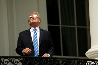 Image: Trump watches the solar eclipse from the Truman Balcony at the White House in Washington