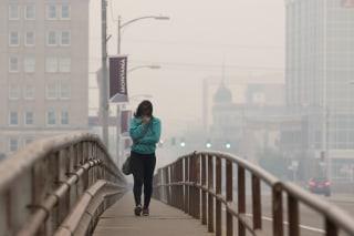 Image: Tatiana Weed walks to work through smoke in Missoula