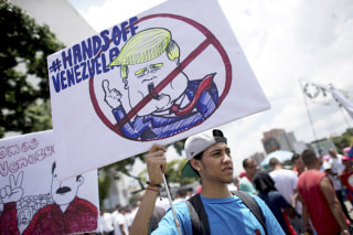 "Image: A government supporter holds a placard with the universal ""No"" symbol over a caricature of U.S. President Donald Trump"