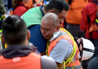 Image: Rescue workers embrace each other deeply moved after a seismic alert sounded in Mexico City on Sept. 23, 2017, four days after the powerful quake that hit central Mexico.