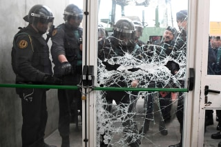 Image: Spanish Guardia Civil guard smash the door of a polling station Catalonia's president was due to vote, early Sunday.