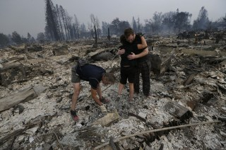 Image: Michael Pond, left, looks through ashes as his wife Kristine, center, gets a hug from Zack Thurston