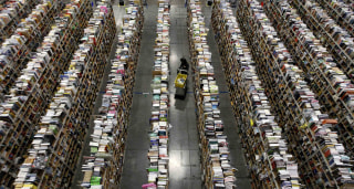 Image: Worker gathers items for delivery at Amazon's distribution center in Phoenix