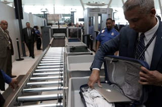 Image: An Airport Official Removes a Laptop