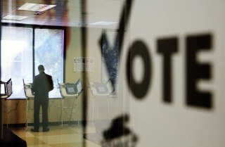 Image: A voter is reflected in the glass frame of a poster while casting a ballot during early voting in Atlanta