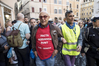 Image: Graziano Cecchini is taken into custody after pouring red paint in the water of the Trevi Fountain