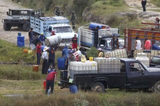 Image: People fill large drums of fuel from a clandestine outlet in San Francisco Tlaloc, Mexico