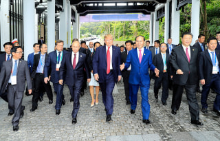 Image: Presidents Trump and Putin walk together with Vietnamese President Tran Dai Quangat the APEC summit on Saturday