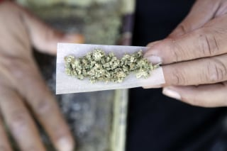 Image: A man rolls a marijuana joint is in San Francisco.