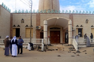 Image: People stand outside Al Rawdah mosque