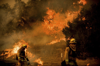 Image: Firefighters light backfire while trying to keep a wildfire from jumping Santa Ana Rd. near Ventura, California, on Dec. 9, 2017.