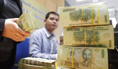 Image: Employees count money at a branch of the BIDV in Hanoi