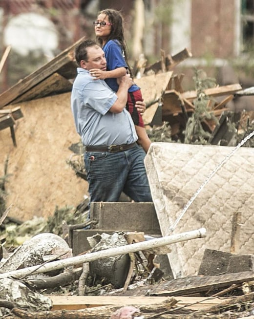 Image: A man holds a girl after she was pulled from the basement of her destroyed home in Pilger, Neb.