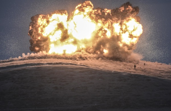 Image: An ISIS militant stands as an airstrike hits an ISIS position on Tilsehir hill near the Syrian-Turkish border on October 23, 2014.
