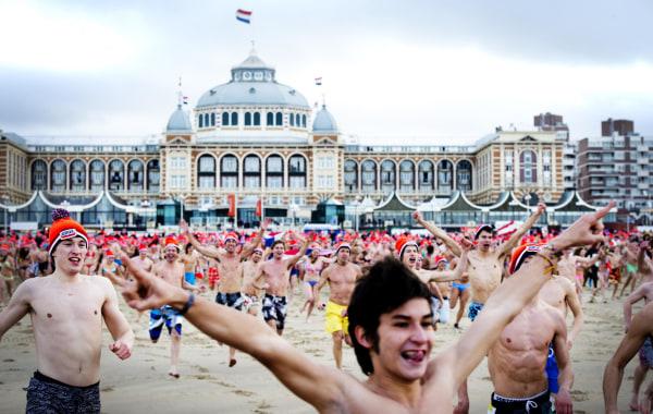 Image: People run towards the sea in Scheveningen, the Netherlands.