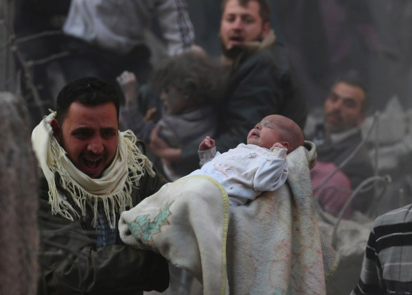 Image: A man carries a baby who survived what activists say was an airstrike by forces loyal to Syrian President Bashar Assad in the Duma neighbourhood of Damascus