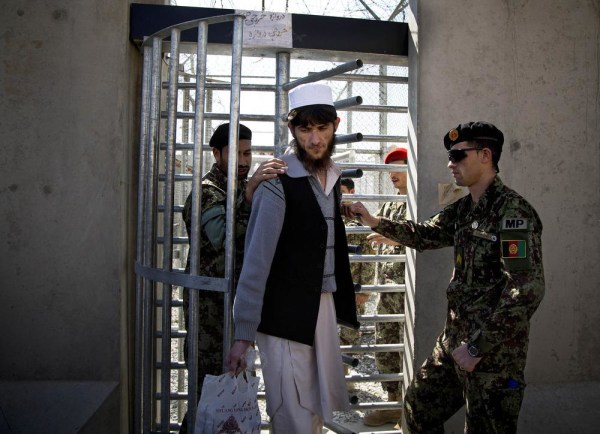 Image: An Afghan prisoner leaves with his belongings from the Parwan Detention Facility.