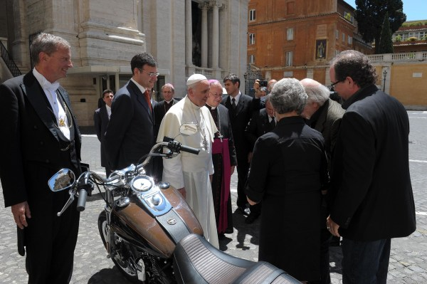 Image: Pope Francis stands by a Harley-Davidson that was donated to him.